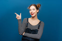 Happy beautiful young woman standing and pointing away royalty free stock photos