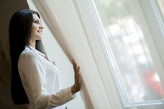 Happy beautiful woman staring out the window. Happy beautiful young woman staring out the window and holding curtains Stock Photo