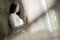 Happy beautiful woman staring out the window Royalty Free Stock Image
