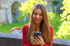 Happy beautiful young woman using smart phone app outdoor royalty free stock photos