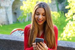 Happy beautiful young woman using smart phone app outdoor royalty free stock photo