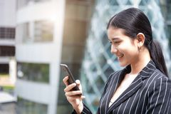 Happy beauty Asian woman looking at smart phone while smiling in urban background. Technology and people lifestyle concept.  royalty free stock images