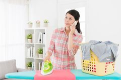 Beauty woman using mobile cell phone calling. Happy beauty business woman using mobile cell phone calling for family when she ironing messy clothing in living stock photo