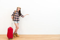 Happy beauty female backpacker with suitcase. Ready to travel and making showing gesture presenting white background looking at camera smiling Royalty Free Stock Images