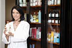 Happy beauty salon employee looking away while holding cosmetic products Stock Photos