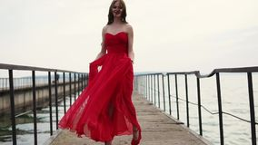 Happy beauty in scarlet dress goes on high red heels along the sea at pier. Beautiful woman with curly hair walks along the pier along the sea, her dress stock video footage