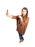 Happy beauty taking selfie while pointing finger at cellphone camera Royalty Free Stock Photo