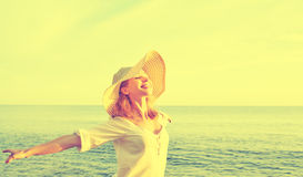 Happy beauty woman in hat opened his hands, enjoys sunset over s Stock Image