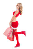 Happy beautyful woman in red santa claus clothes with shopping bags Royalty Free Stock Photography