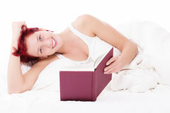 Happy in bed reading a book Stock Images