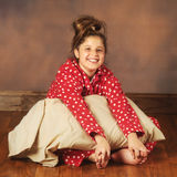 Happy for Bedtime. A happy preteen in polka-dot pajamas sitting on a hardwood fllor while hugging her pillow Royalty Free Stock Photos