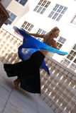 Happy belly dancer. Smiling attractive blonde belly dancer twirling with veil on balcony outside buildings Stock Image