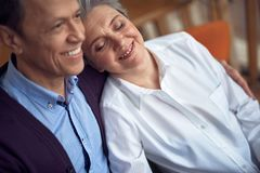 Happy beloved aged couple enjoying to be together. Enjoyable meetings. Close up portrait of happy smiling aged men embracing women putting head on his shoulder stock photography