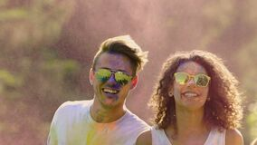 Happy best friends dancing and jumping in colorful dust clouds at Holi festival. Stock footage stock footage
