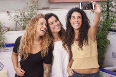 Happy best friends making selfie on mobile or smart phone with a royalty free stock photography