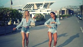 Happy best friends or sisters dancing and posing. And showing lovely relationship. They look happy. They have same jeans stock video