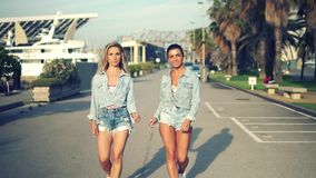 Happy best friends or sisters dancing and posing. And showing lovely relationship. They look happy. They have same jeans stock video footage