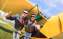 Happy best friends taking selfie at aeroclub with ultra light airplane. Luxury friendship concept about young people with thumbs up having fun together stock photos