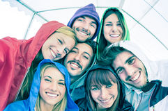 Happy best friends taking selfie wearing hoodies outdoors Stock Photography