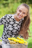 Happy bicyclist. Happy smiling bicyclist with bunch of flowers royalty free stock photo