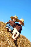 Happy Big Brother and Baby Sitting on Hay Bale Outside Stock Photos
