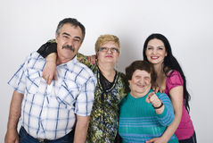 Happy big  family. Happy family with  three generations of women grandmother,mother ,daughter and father  posing in a big embrace ,elderly woman pointing to you Royalty Free Stock Photography