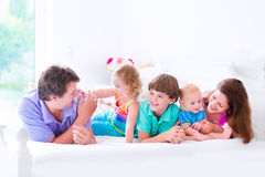 Happy big family in a bed. Happy big family, young parents with three kids, laughing boy, cute toddler girl and adorable little baby wearing colorful pajamas stock photography