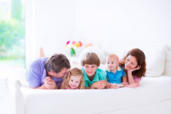 Happy big family in a bed. Happy big family, young parents with three kids, laughing boy, cute toddler girl and adorable little baby wearing colorful pajamas Stock Images