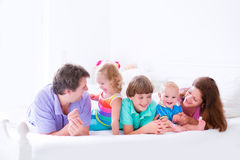 Happy big family in a bed. Happy big family, young parents with three kids, laughing boy, cute toddler girl and adorable little baby wearing colorful pajamas royalty free stock images