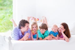 Happy big family in a bed. Happy big family, young parents with three kids, laughing boy, cute toddler girl and adorable little baby wearing colorful pajamas Royalty Free Stock Photo