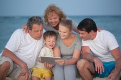 Happy big family with tablet PC on the beach. Child using tablet computer and his big family including parents and grandparents looking at screen. They sitting Royalty Free Stock Photography