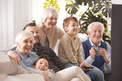 Happy big family watching tv. Happy big family sitting on sofa and watching tv together Royalty Free Stock Photos