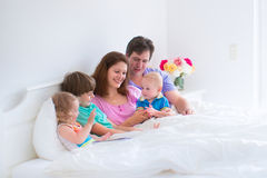 Happy big family in a white sunny bedroom. Happy big family, young parents with three kids, laughing boy, cute toddler girl and adorable little baby wearing Stock Image