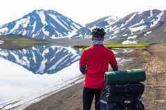 Happy biker on backdrop of lake and snowing mountains in Iceland Royalty Free Stock Photos