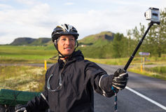 Happy biker doing selfie on backdrop of mountains in Iceland Stock Photography