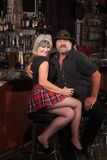 Happy Biker Gang Couple in Bar. Happy middle aged motorcycle gang couple sitting at bar counter Stock Photos