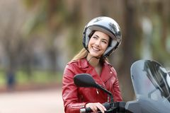 Happy biker on a motorbike dreaming looking above. Happy biker wearing helmet sitting on a motorbike dreaming looking above on the street Royalty Free Stock Photo