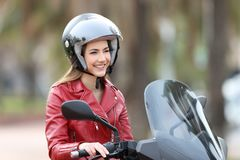 Happy biker on a motorbike looking away. Happy biker sitting on a motorbike looking away on the street Royalty Free Stock Image