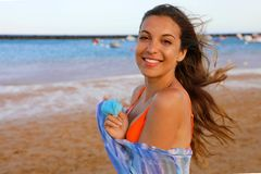 Happy bikini woman on the beach. Portrait of beautiful girl with wind fluttering hair and pareo. Summer portrait on the beach at. Sunset. Young pretty smiling royalty free stock images