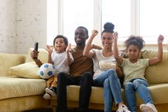 Happy biracial family with kids watch football at home together