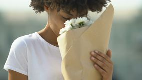 Happy biracial female holding bouquet of white flowers and sincerely smiling. Stock footage stock footage
