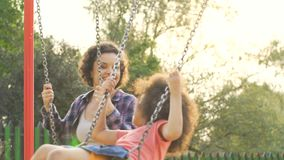 Happy biracial mother and daughter swinging, spending time together, slow-motion. Stock footage stock video footage
