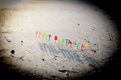Happy birth day letter candles in the sand. With the sea royalty free stock photo