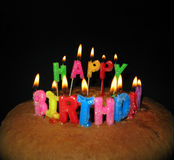 Happy Birthday. Lighted candles on a birthday cake on black background. The focus is on the word HAPPY Royalty Free Stock Photo
