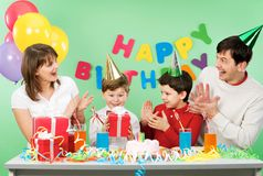 Happy birthday. Portrait of boy holding his present with happy parents and brother near by stock image