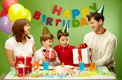 Happy birthday. Portrait of boy holding his present with happy parents and brother near by stock photos