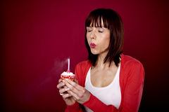 Happy Birthday. A beautiful woman is blowing out a candle on a cupcake and making a wish for her birthday Stock Photos