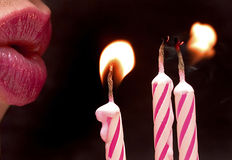 Happy birthday!. Close-up of lips blowing out pink candles Stock Photos
