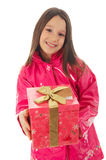 Happy birthday. Young girl in a pink raincoat giving a present to the camera Royalty Free Stock Photos