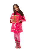 Happy birthday. Young girl in a pink raincoat holding a present Stock Image